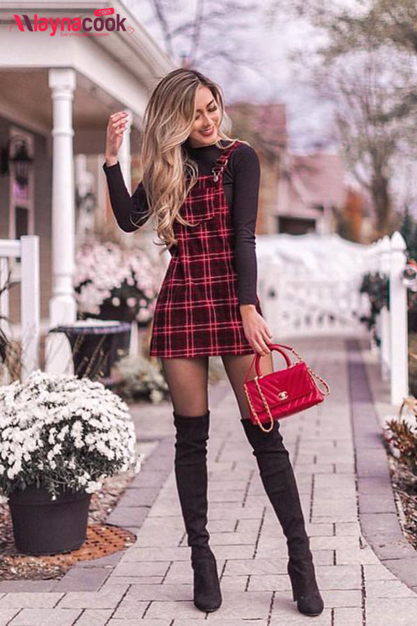 a black sweatshirt checkered dress red bag black boots